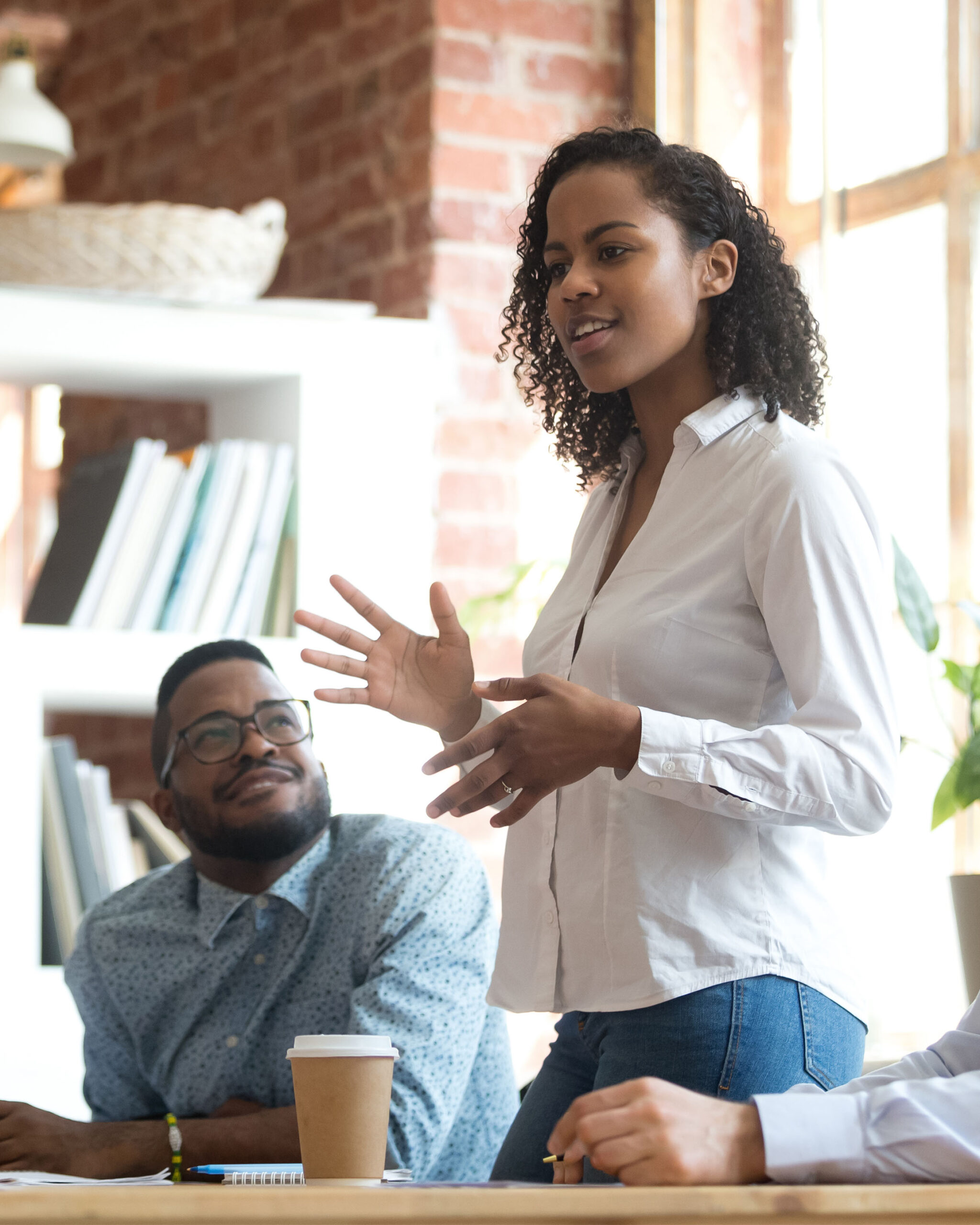 Image of young African American woman presenting to colleagues at a work meeting